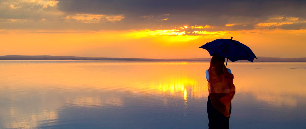 Woman with umbrella watching a sunset over water